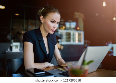 Woman professional economist checking e-mail on laptop computer while sitting in restaurant during work break in company. Female experienced business writer for executive summary using netbook