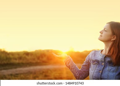 Woman with profile view stretched out his hand and catches sunrize. Tourism, vacation, holiday, healthy lifestyle concept.
