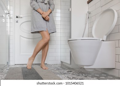 Woman with prostate problem in front of toilet bowl. Lady with hands holding People wants to pee - urinary incontinence concept