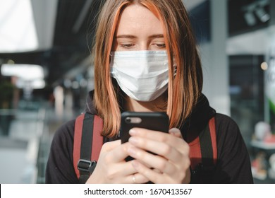 Woman in protective face mask using the phone at a public place. Coronavirus, COVID-19 spread prevention concept, responsible social behaviour of a citizen