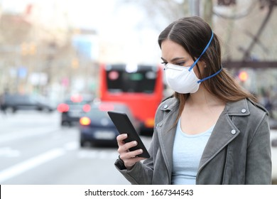 Woman with protective mask avoiding pollution using smart phone with city traffic background