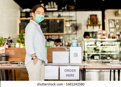 Femme portant un masque de protection achetant de la nourriture et des boissons dans un café à emporter