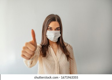 Woman with protective mask showing thumb up, and looking at camera. Woman with face mask protection of Coronavirus in human lungs. MERS-CoV, SARS, Adenoviruses and other respiratory viruses