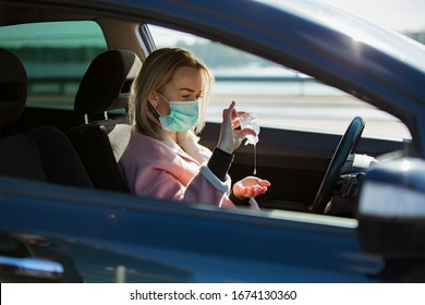 Woman in protective mask sitting in a car on road, using hand sanitizer. Safe traveling.