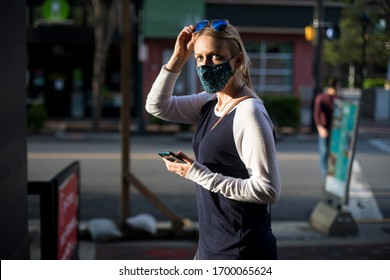 A woman protects herself from COVID-19 by wearing a mask and sunglasses when she is outside.