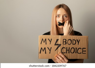 A woman protests against the ban on abortion in Poland. A feminist defends women's rights. Conceptual photo with protest symbols.