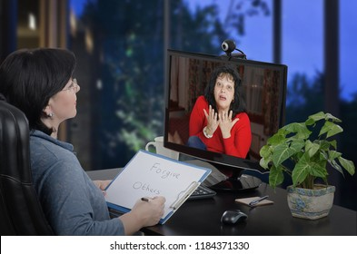 Woman psychiatrist runs tele psychologist session online. A mature woman in red jersey is in stress and panic on the other end. She tries to explain something using hands. Doctor attentively listening