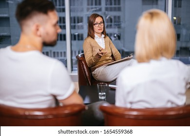 woman psychologist consulting young family consisted only of man and woman in modern office, couple can't get along with each other, troubles in relationships, so male and female visit psychologist