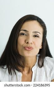 Woman puckering lips, looking at camera, portrait