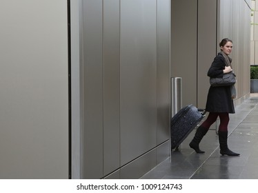 Woman pulling bag on wheels