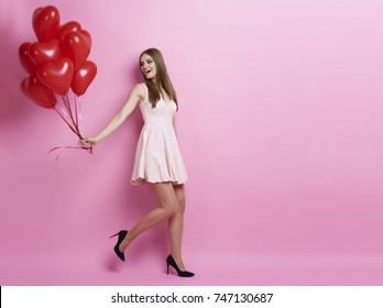 Woman pulling bunch of balloons
