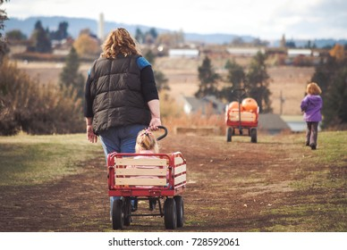 Woman pulling child in red wagon with wagon full of pumpkins in front of them