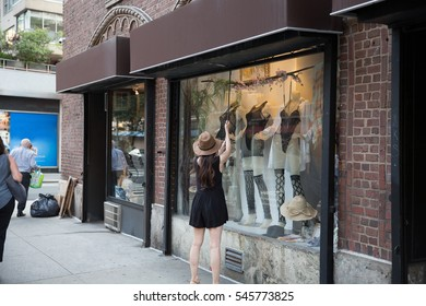 woman pulling gate down - closing clothing store after hours in Manhattan NYC