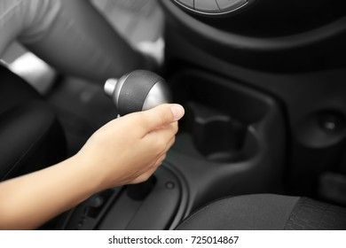 Woman pulling gearshift lever in car