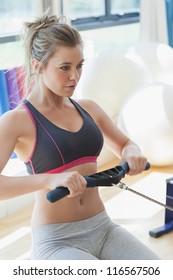 Woman pulling on row machine in fitness studio