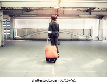 Woman pulling suitcase at airport terminal