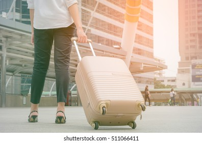 Woman pulling suitcase in modern city ,vintage tone style