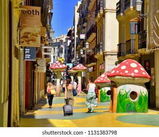 Woman pulling suitcases along the famous Mushroom street in Alicante city. Costa Brava, Spain, Europe. July 2018