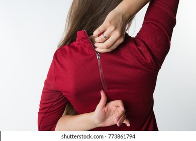 Woman pulling the zip up or down on her stylish red dress .