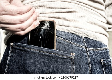Woman pulls a broken mobile phone up from her pocket jeans pant after sitting over it. Carelessnes about gadgets concept