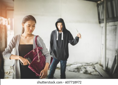 Woman pulls a gun from her swanky purse while the thief stood in the back. Conceal carry weapon for protection themselves concept. Selective focus.