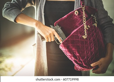 Woman pulls a gun from her swanky purse. Conceal carry weapon for protection themselves concept. Selective focus to gun.