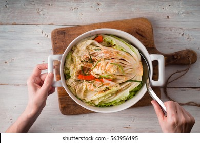 Woman pulls kimchi from ceramic bowl top view