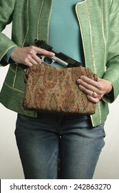 Woman pulls a large gun from her swanky purse