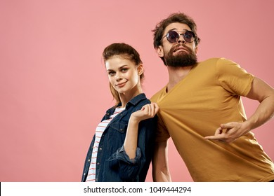 woman pulls a man for a T-shirt, glasses