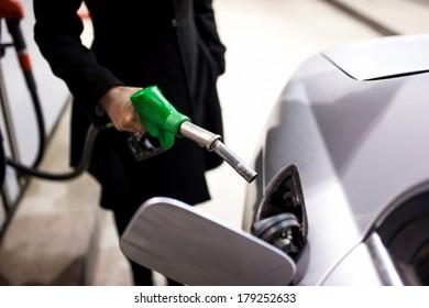 Woman pumping gas at petrol station