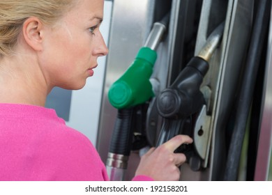 Woman pumping gasoline fuel in car at gas station. Petrol or gasoline being pumped into a motor vehicle car.