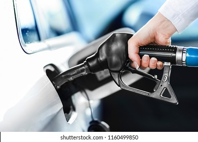 Woman pumping petrol at gas station into vehicle. Hand holding a pistol or nozzle pump prepare to refuel car with gasoline.