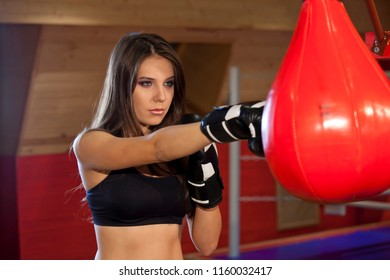 Woman punches traning bag in boxing gloves