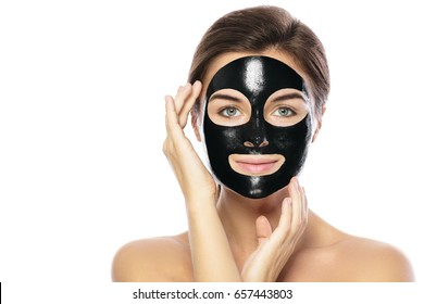Woman with purifying black mask on her face isolated on white background