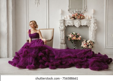 woman in purple evening dress sits in chair