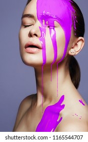 woman in purple paint. liquid paint flowing over a beautiful face and Body. Colorful portrait of Girl in Paint