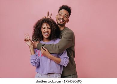 Frau in violettem Pullover-Weinbau. Paar mit Friedenszeichen auf rosafarbenem Hintergrund. Attraktive Mädchen und ihr Freund in braunem Hemd lächeln auf isoliert
