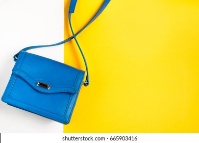 Woman purse on colorful background. Blue and yellow pastel colors, top view