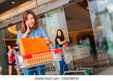 Woman push shopping cart in supermarket. Beautiful woman enjoying shopping. Girls having fun.