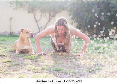 Woman push ups with her dog in garden