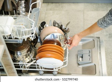 The woman pushed the dirty dishes in the dishwasher machine.