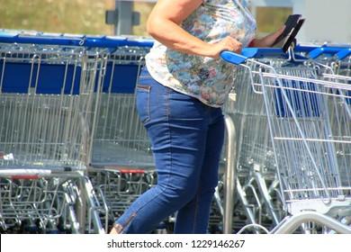 Woman pushes shopping cart for shopping