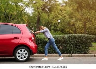 Woman pushing broken car on road along city street