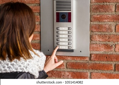 Woman pushing the button and talking on the intercom