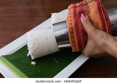 Woman pushing hot Puttu or Pittu holding metal Puttu Kutti vessel in hand. Popular South Indian steamed breakfast dish made of rice flour, grated coconut Kerala, India. Sri lankan food on banana leaf.