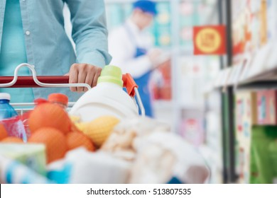 Woman pushing a shopping cart and doing grocery shopping at the supermarket, hand detail closeup