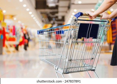 woman pushing shopping cart in shopping mall