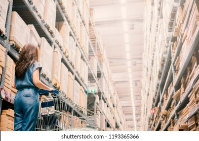 Woman pushing a shopping cart and standing in Warehouse aisle and Sells ready to assemble furniture appliances and home accessories. copy space