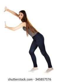 Woman pushing something imaginary isolated over a white background.