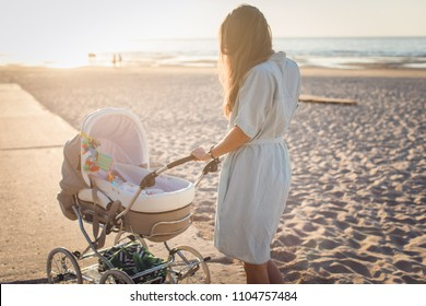 Woman pushing stroller outdoors. Taking her little one for a summer walk